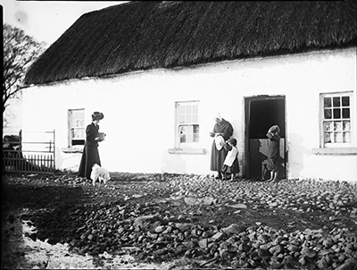 Edith Dillon carrying a box camera, approaching woman and 2 children standing outside thatched cottage